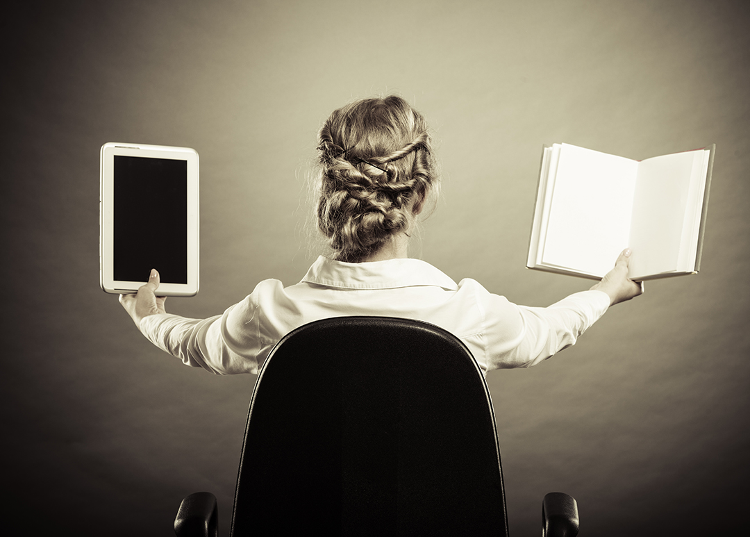 A woman holding up an e-reader and a paper book, comparing them.